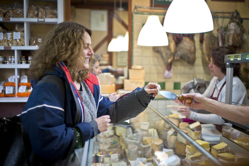 Raúl dando a probar a una clienta de León, un queso de su tierra