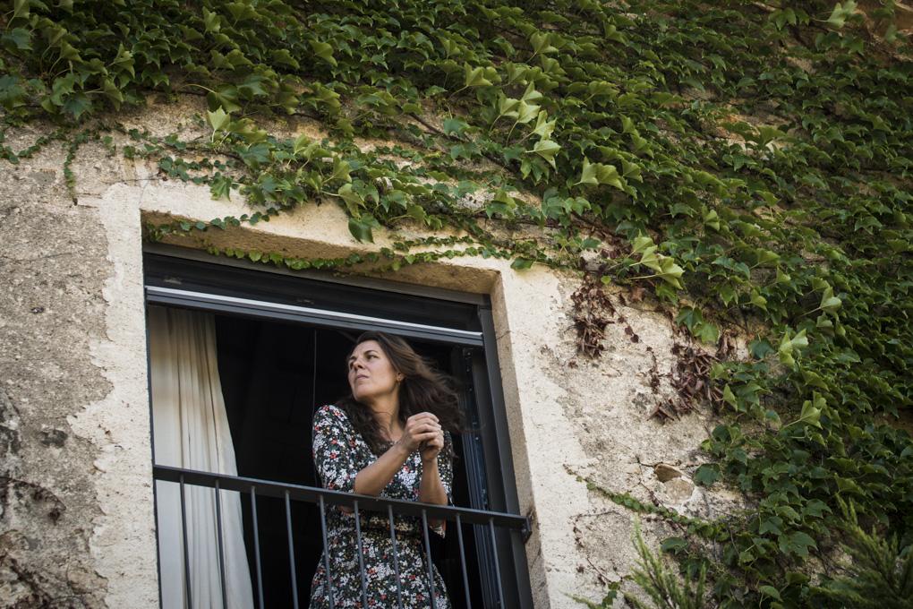 mujer de melena larga disfruta del paisaje asomada a la ventana