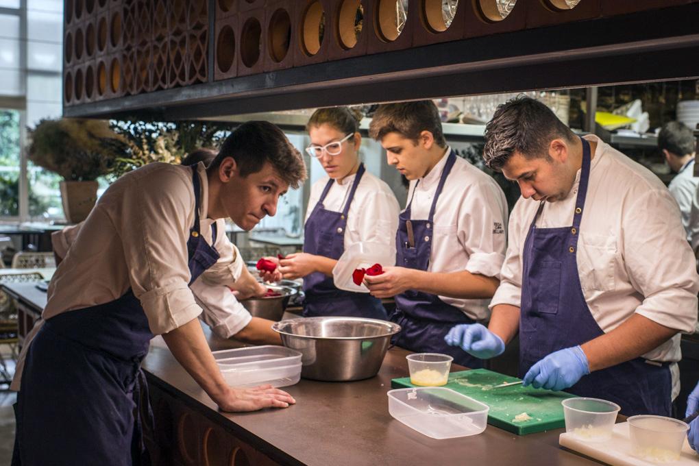 tres cocineros deshojan rosas en la cocina abierta de Disfrutar
