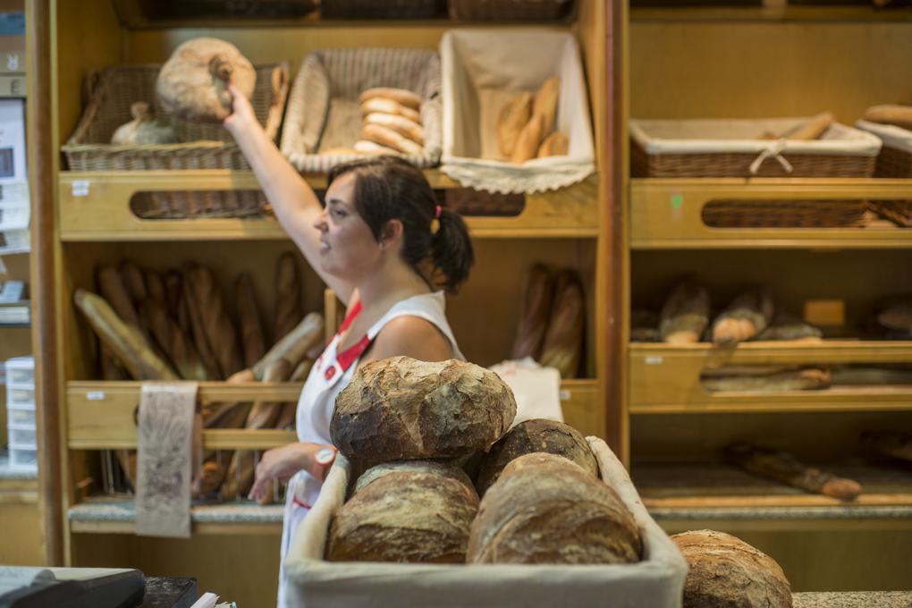 Una dependienta escoge un pan en el despacho de la panadería