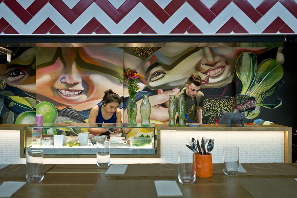 Mural de colores caribeños y dos cocineros trabajando en un plato