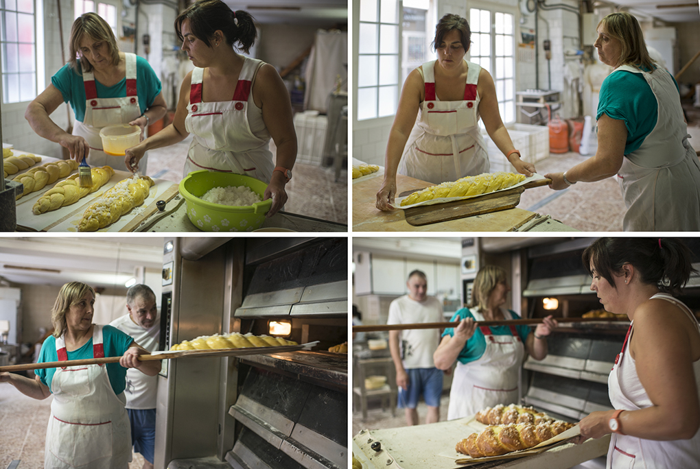 Dos panaderas meten en el horno las trenzas dulces para ser horneadas.