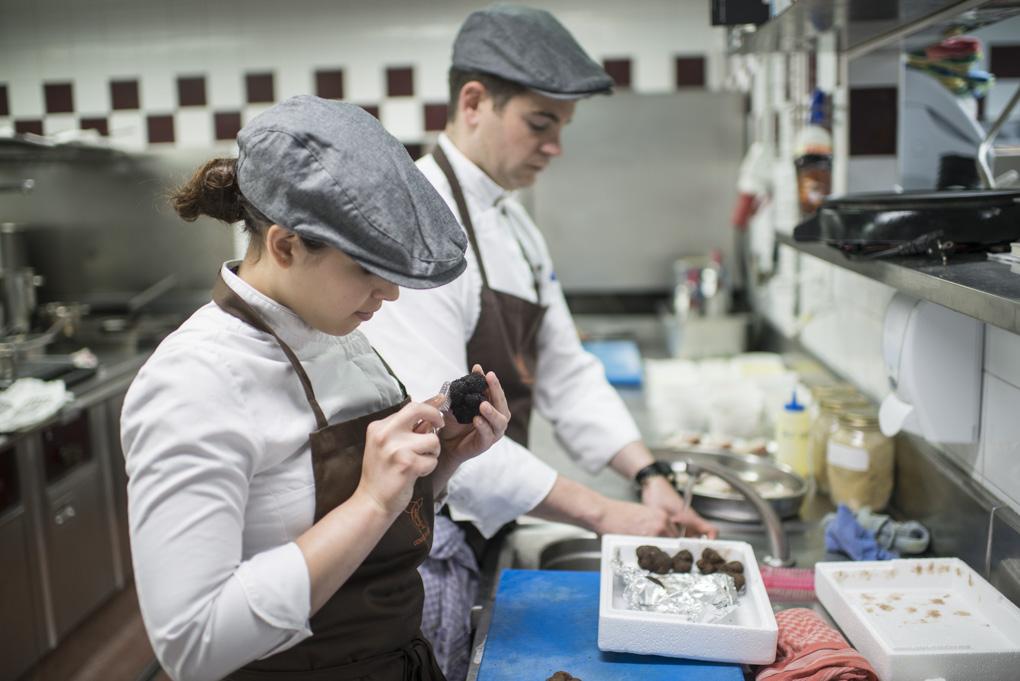 Un par de cocineros limpian trufas en la cocina