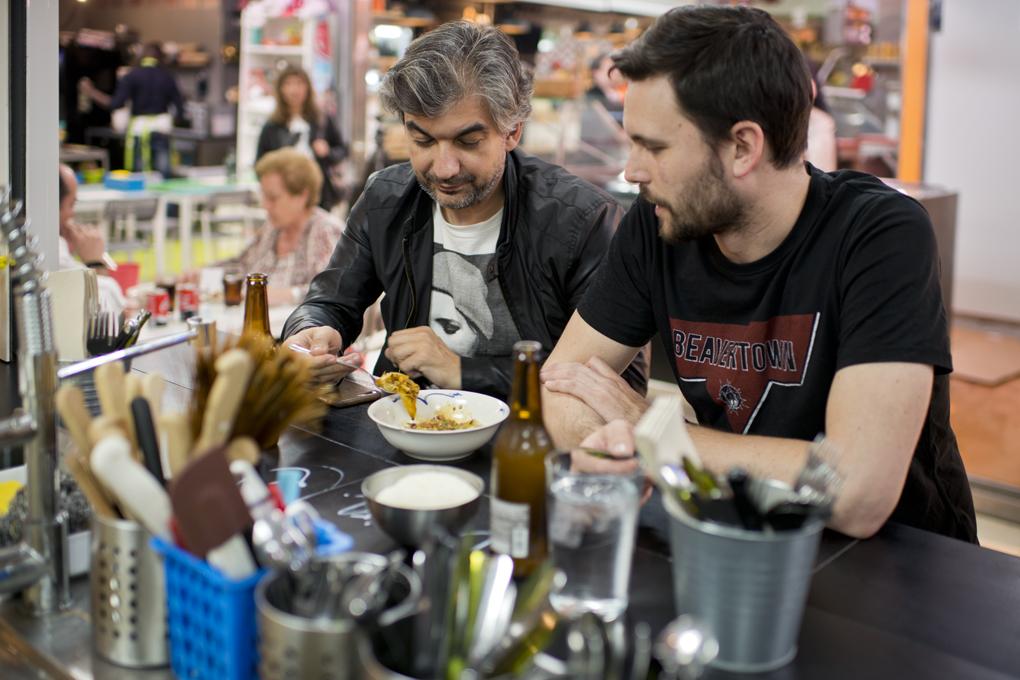 Dos amigos comen en la barra el plato de dumplings