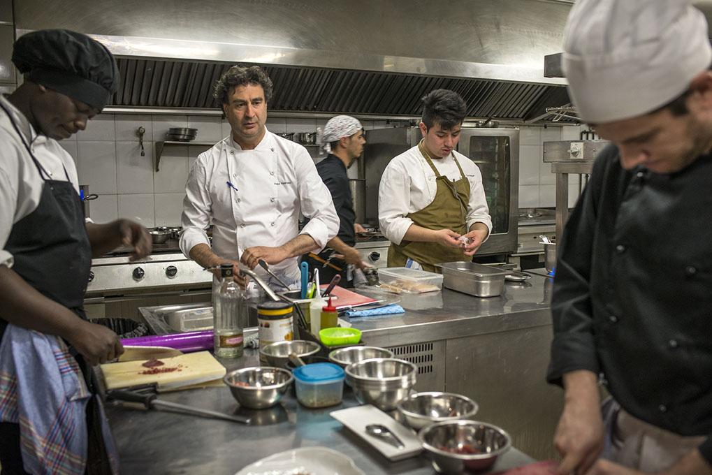 Pepe Rodríguez en medio de la cocina rodeado de su equipo faenando