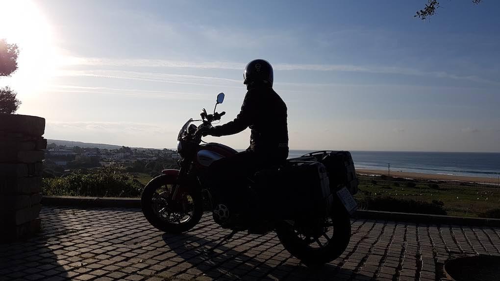 Con la moto y la playa de Bolonia al fondo. Foto: Clara Peñalver