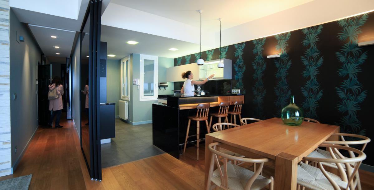 Vista de la entrada, el salón y la cocina, con papel pintado de hojas grandes estampadas