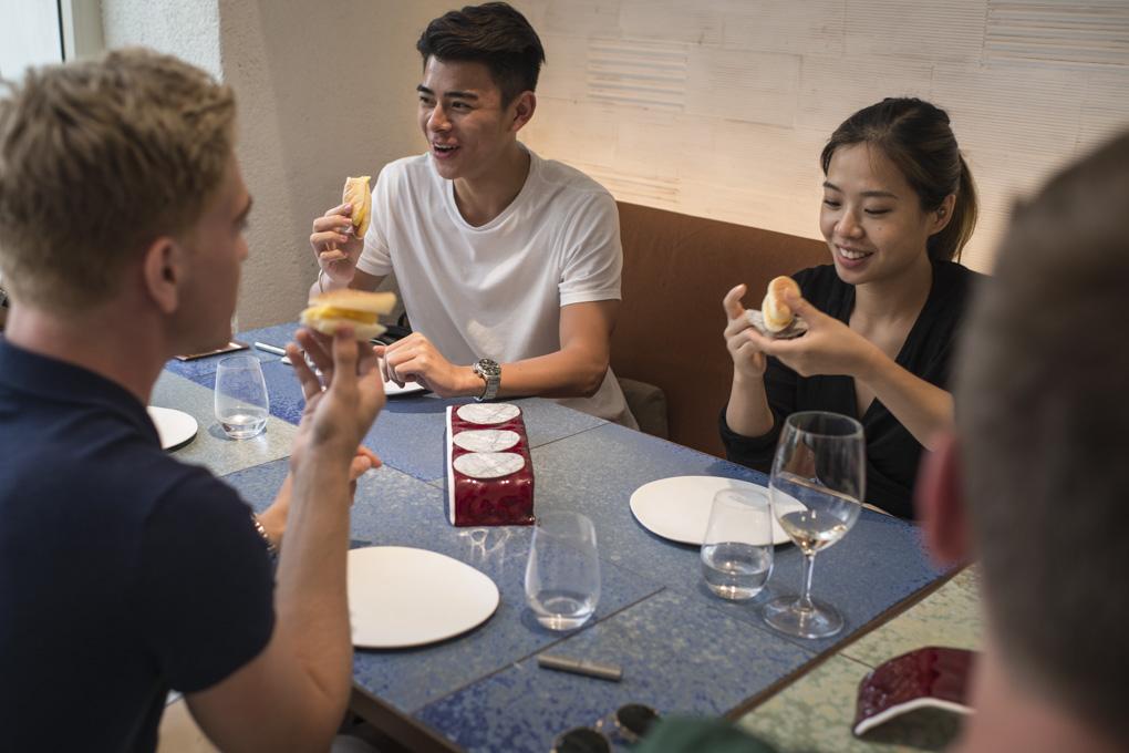 Un grupo de jóvenes extranjeros con caras de felicidad mientras toman un postre