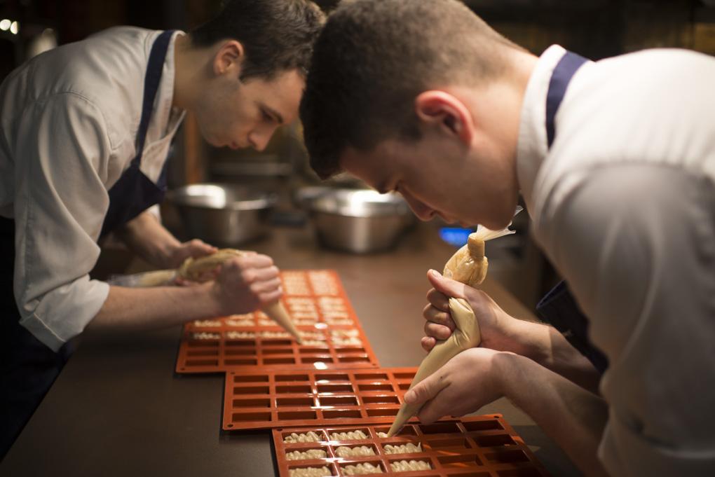 Dos cocineros rellenan unos moldes