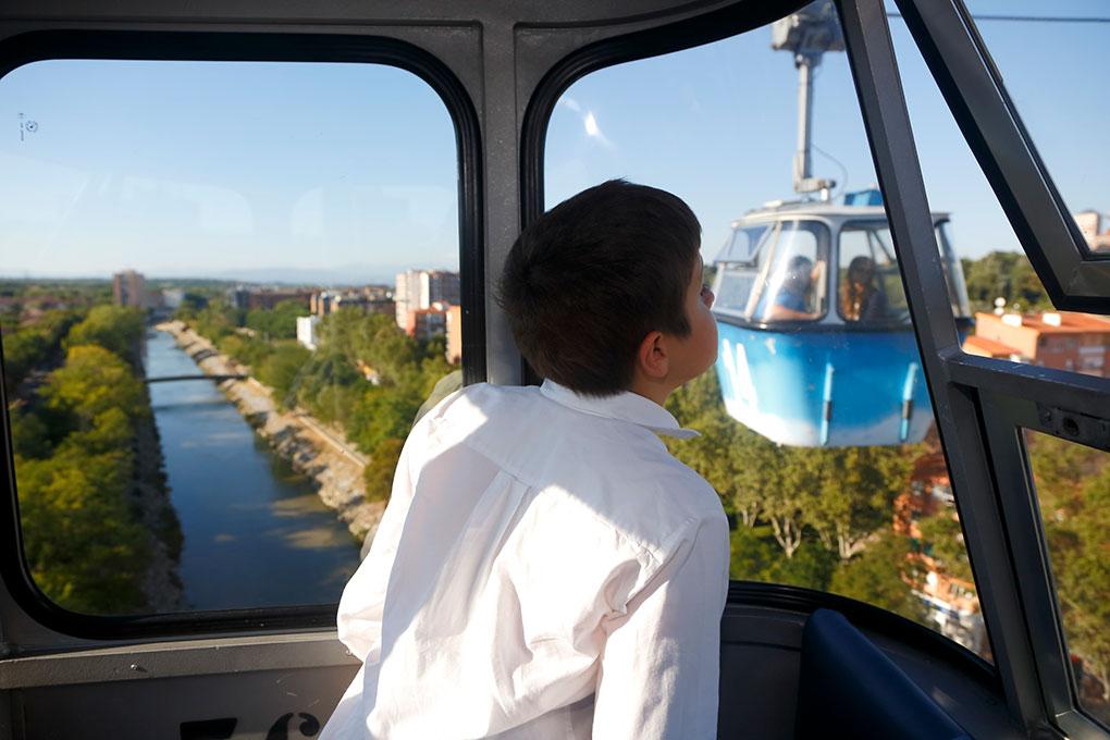 El niño mira por la ventana y se cruza con otra cabina