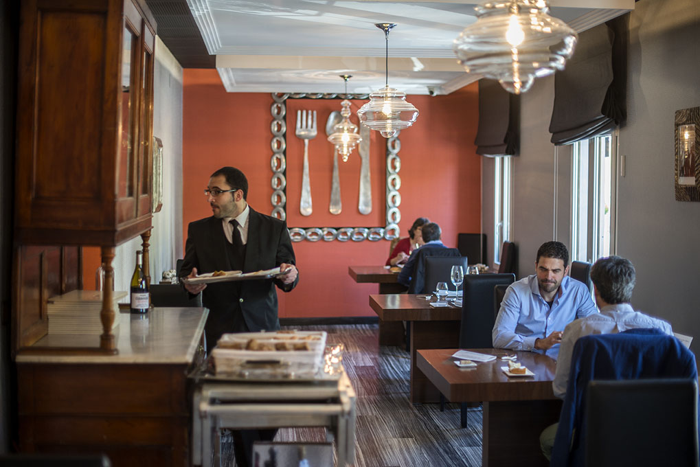 El comedor, con dos mesas ocupadas pro sendas parejas y un camarero sirviendo