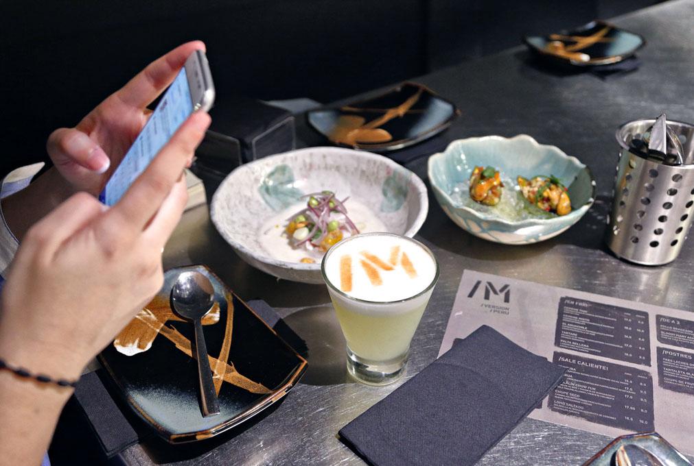 Una chica fotografía con el móvil dos platos de Barra M