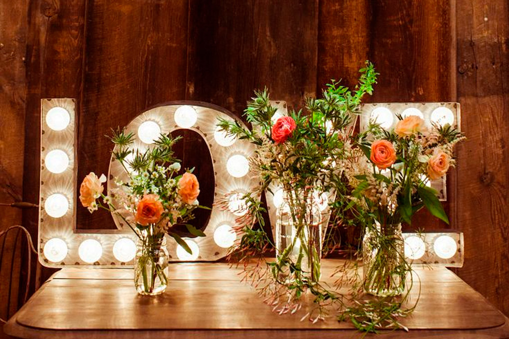 Cartel Love iluminado con flores
