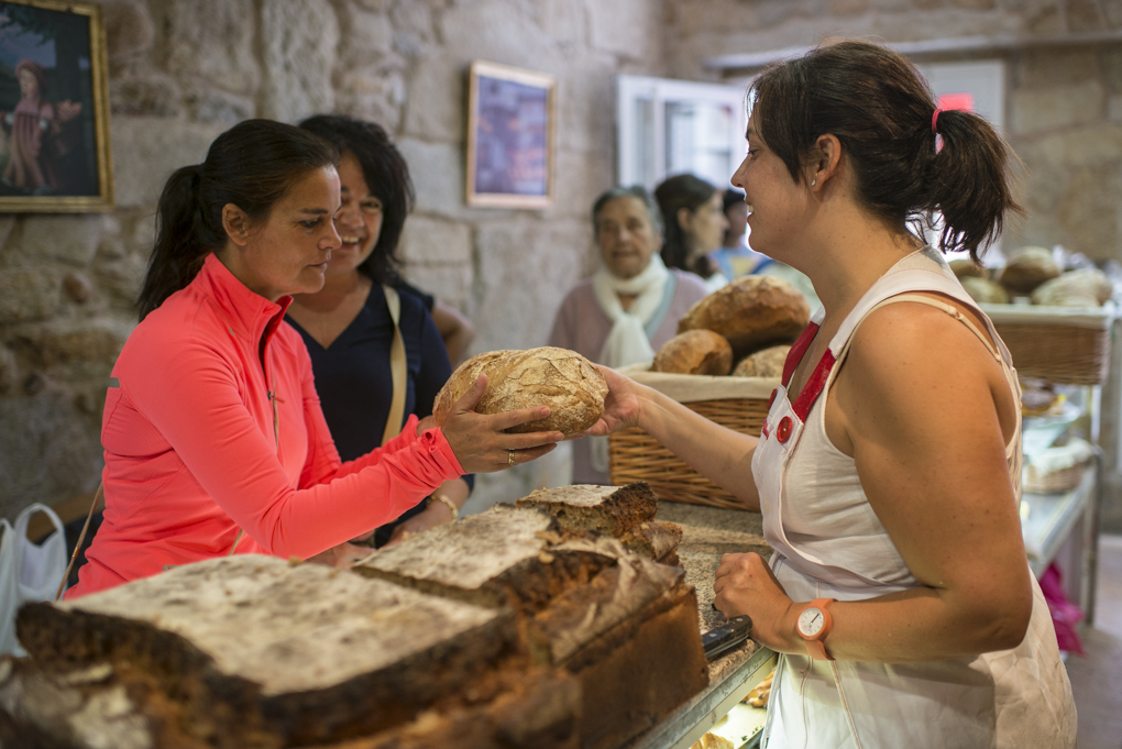 Una clienta coge el pan y lo observa en la panadería.