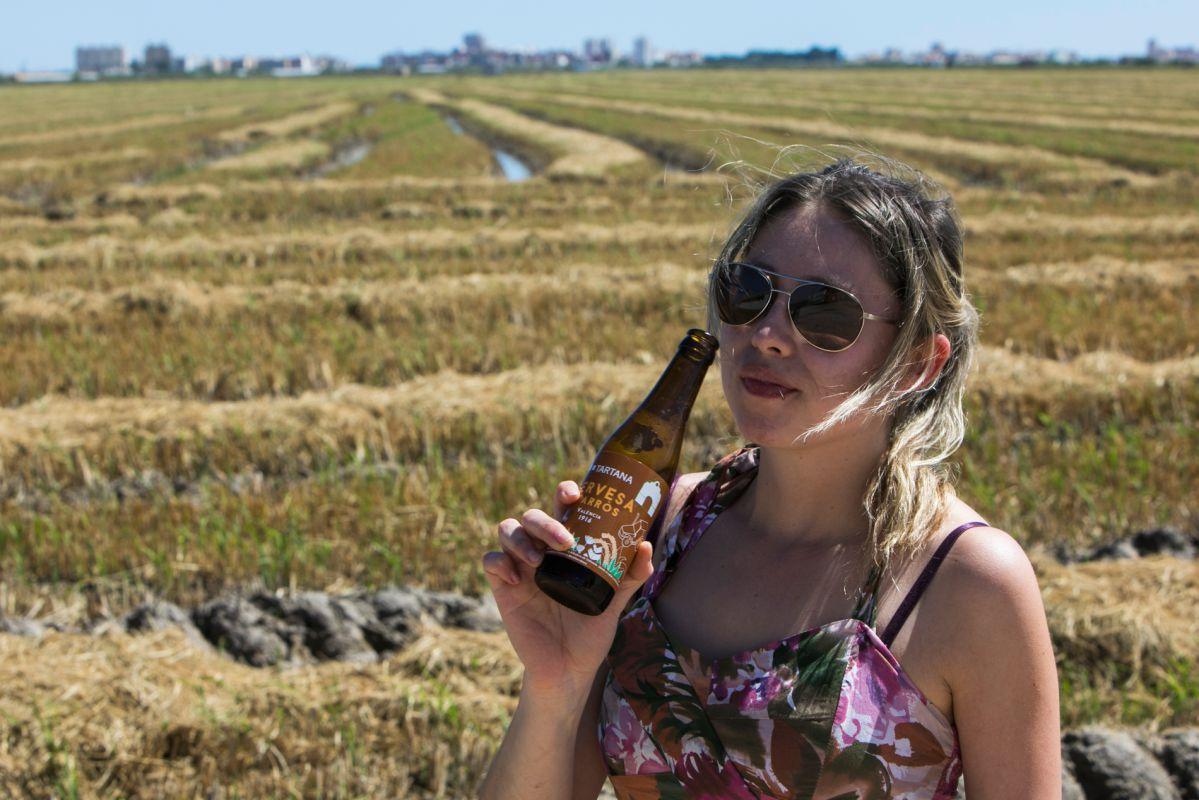 Una chica bebe cerveza de arroz en L'Albufera. Foto: Eva Máñez