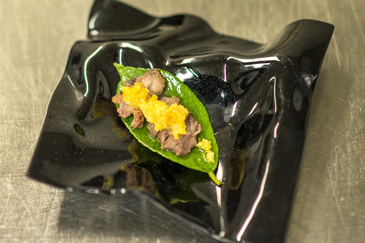 Carrillera de cordero sobre hoja de limonero y mole de naranja en salmuera, piñones y aove. Foto: Alfredo Cáliz