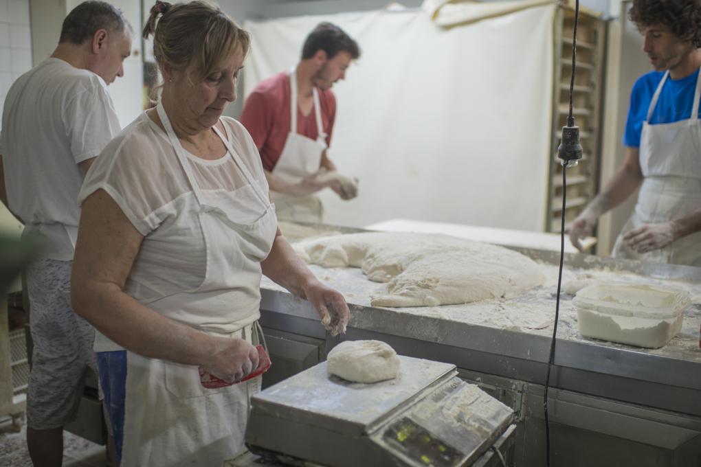 La panadera pesa cada pedazo de masa en un peso en el obrador