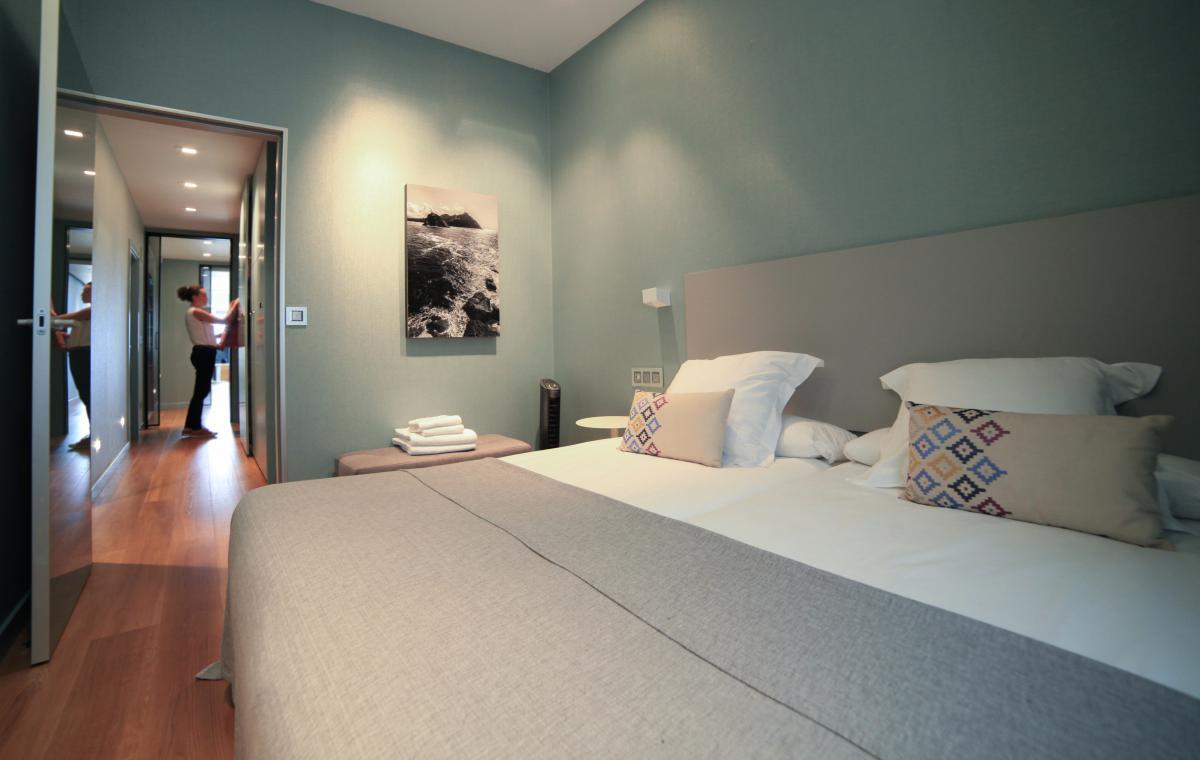una cama primorosamente hecha en una habitación despejada