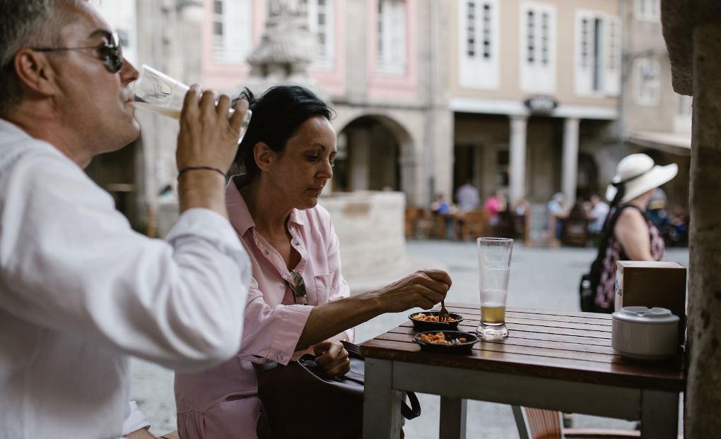 Tomarse un vino y una tapa en la terraza de la Adega, en los soportales de la plaza do Campo