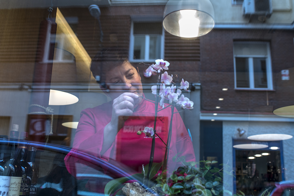 Marian retoca las flores que se asoman al ventanal