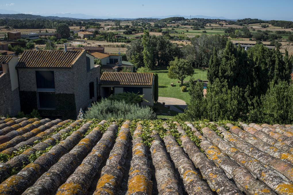 vista del campo y los tejados del pequeño pueblo medieval desde la masía