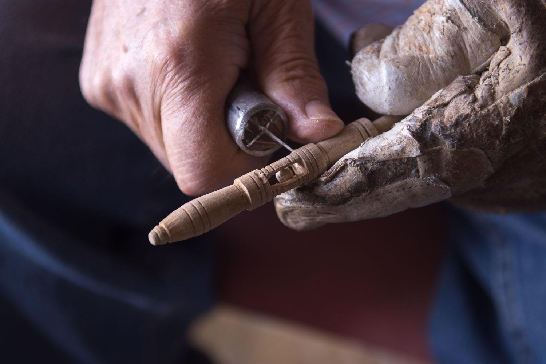 Francisco talla a mano un bolillo de olivo