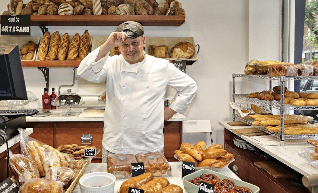 Jorge, el dueño de Casabe Bakery con sus panes, plano medio. Foto: Roberto Ranero