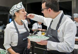 El chef Paco Morales, dando de probar un plato a una cocinera.