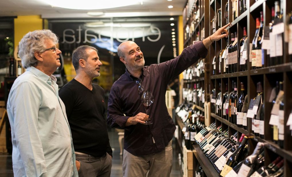 Los clientes de la vinoteca Enópata miran las botellas expuestas en la tienda (Valencia). Foto: Eva Máñez